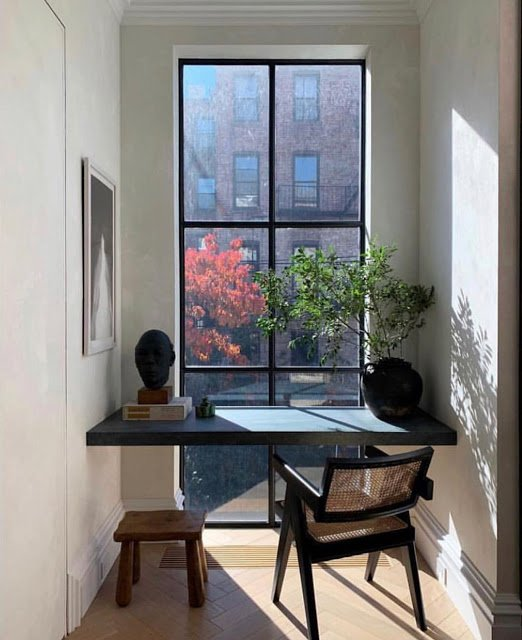 home office in a small space by window at the end of a hallway