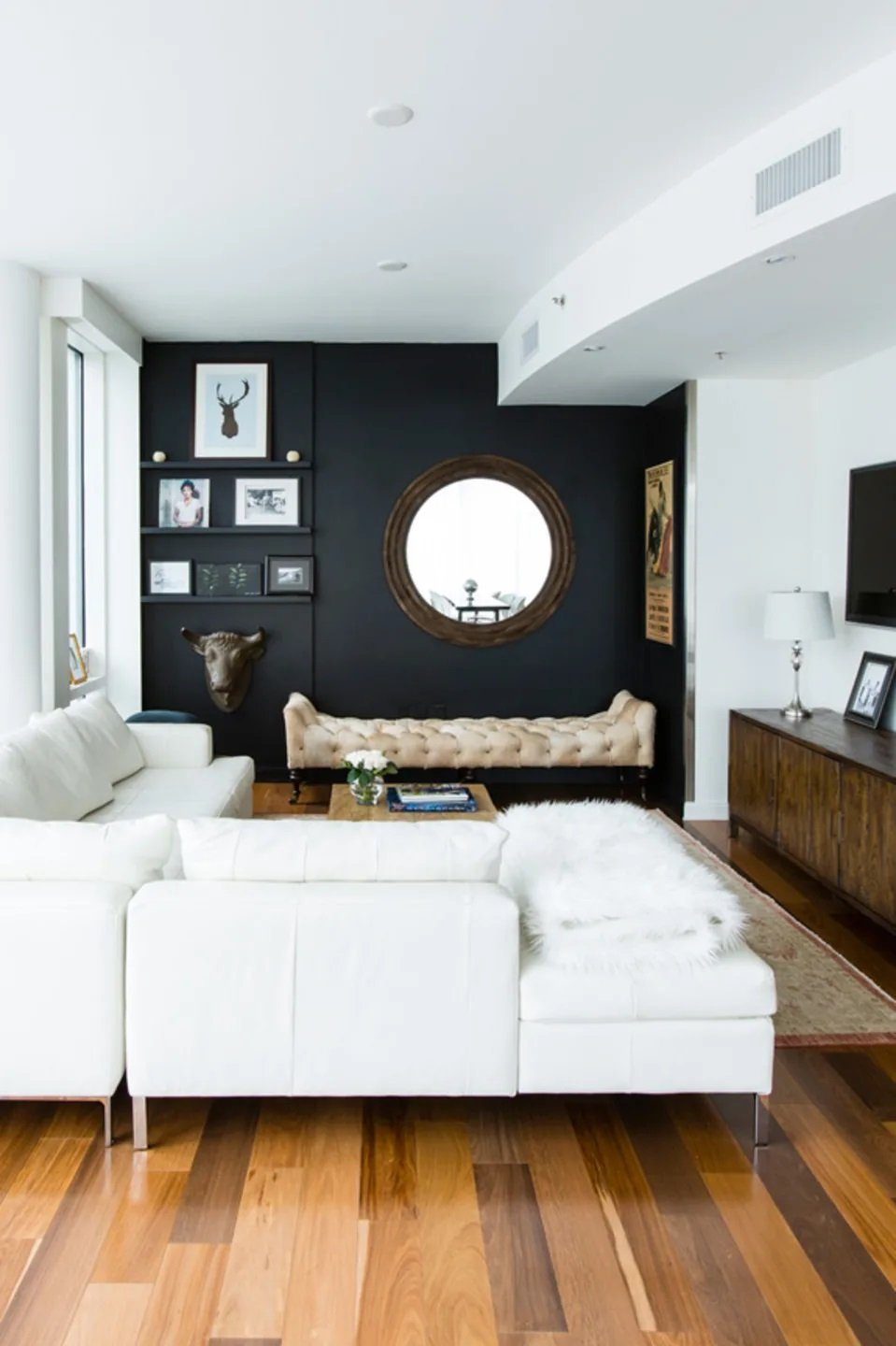 black accent wall and white furniture in small living room