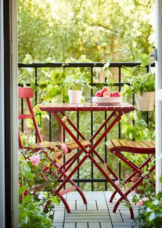 Simple balcony decor with small wooden bistro set and plants